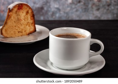 Cup of coffee with cream with a slice of freshly baked homemade muffin