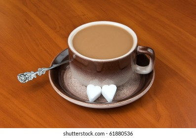 Cup of coffee with cream and sugar on table.