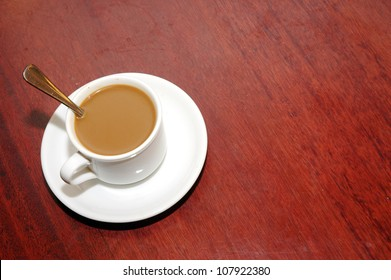 a cup of coffee with creamer on the table