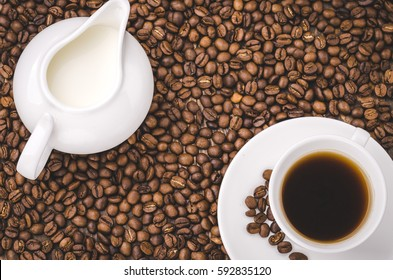 cup of coffee and creamer on a wooden background top view/creamer and cup on coffee grains