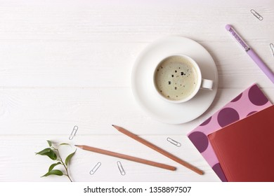 cup of coffee with crema and stationery on wooden background top view.