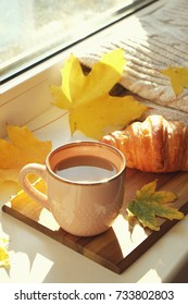 A cup of coffee, croissant, autumn leaves on windowsill with knit sweater. Autumn mood, autumn still life. Hugge concept