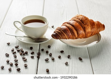 A cup of coffee and a croissant on a table with sprinkled coffee beans. Coffee and croissant close-up. Light breakfast concept.