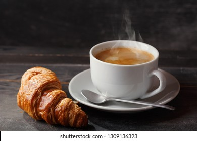 cup of coffee and croissant on wooden table