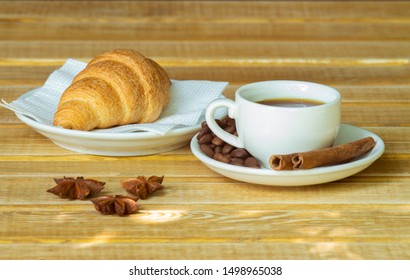 Cup of coffee and croissant on a wooden table for breakfast