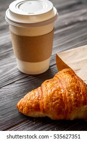 cup coffee and croissant in paper bag on wooden background