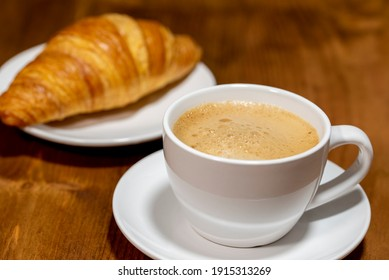 cup coffee and croissants on a wooden dark background