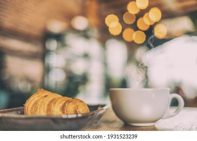 cup of coffee, croissants, on a wooden surface with bokeh background