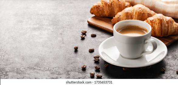 cup of coffee and croissants standing  on wooden board placed on old rustic background
