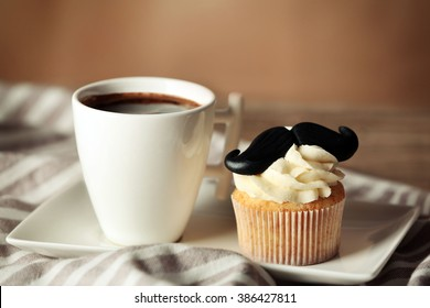 Cup of coffee and cupcake with mustache on napkin closeup