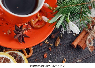 Cup of coffee is decorated by cookies, snowdrops and spices on a wooden table