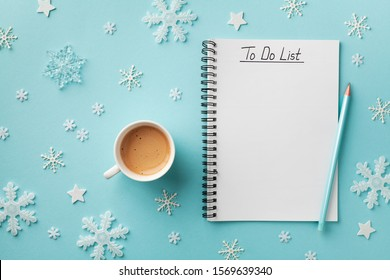 Cup of coffee, decorative snowflakes and notebook with to do list on turquoise background top view, Christmas and winter planning concept. Flat lay.