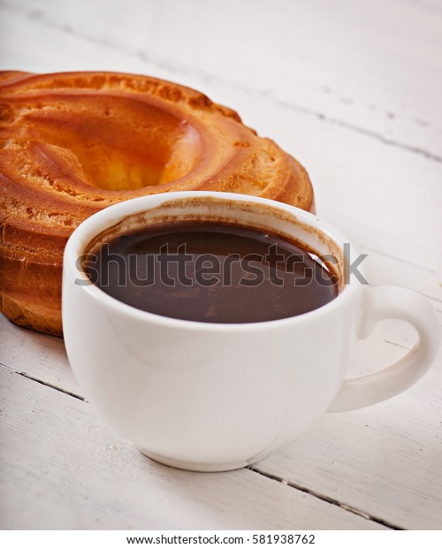 Cup of coffee and delicious baked cookies on old wooden background.