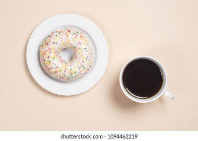 Cup of coffee and delicious donut with frosting and decorated colorful sprinkles in plate on a light brown background, top view