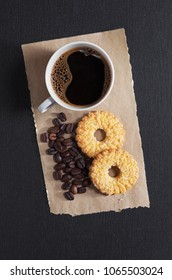 Cup of coffee and delicious shortbread cookies on black stone background, top view