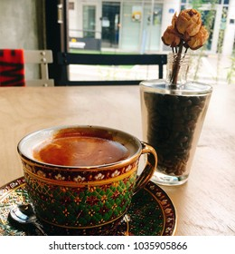 a cup of coffee with dried flowers