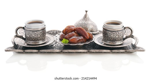 Cup of coffee with dry dates and metal oriental tray isolated on white background
