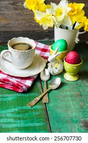 Cup of coffee, easter eggs and bunny on the old wooden table