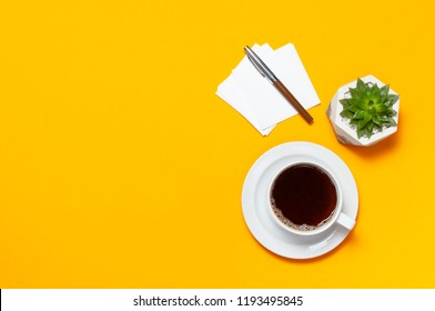 Cup of coffee, empty sheets of paper, pen, flower cactuses succulents on bright yellow minimalistic background, top view Flat Lay with copy space. Overhead shot of empty office desk, Still life