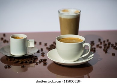 Cup of coffee, cup of espresso, latte macchiato, brown background