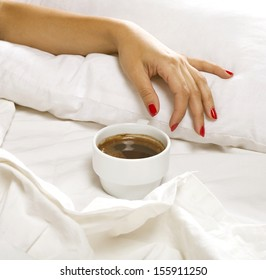 A cup of coffee and female hand on a white sheets