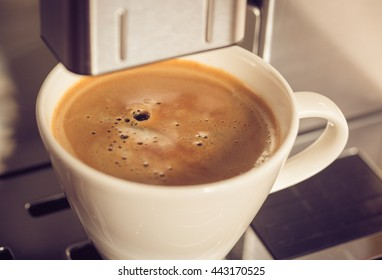 A cup of coffee filled with fresh cooked coffee in a coffee machine. Filtered with soft pastel colors.