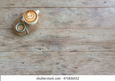 A cup of coffee with flower latte art pattern in a white cup with a cookie on wooden background
