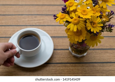 a cup of coffee with flowers on the table in the balcony. enjoy holiday time at the hotel or house