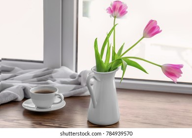 Cup of coffee with flowers on window sill