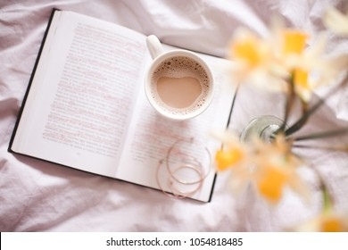 Cup of coffee with flowers staying on opn book in bed. Good morning. Top view.