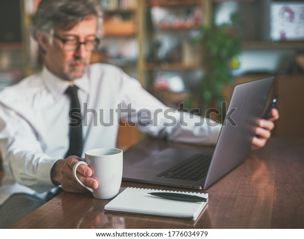 cup of coffee in the foreground next to a notebook and a pencil, scene of a businessman working from home smartly, blurred background