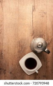 A cup of coffee and french press on wood background top view .