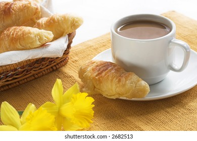 cup of coffee with fresh croissants