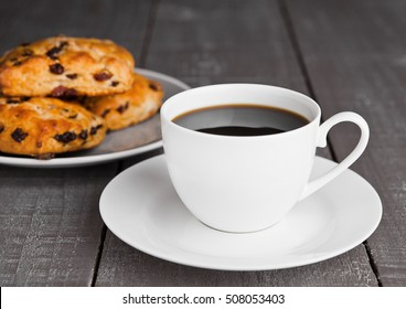Cup of coffee with fresh fruit scones with raisins on wooden table