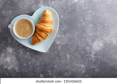 Cup of coffee and freshly baked croissants on gray background. Top view. Copy space.