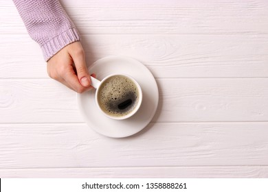 Cup of coffee with frothy in female hands on wooden table. Top view.