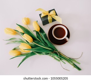 Cup of coffee, a gift box with ribbon and bouquet of yellow tulips isolated on white background. Flat lay, top view.