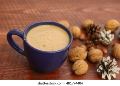 Cup of coffee and  gifts with leafs on wooden background