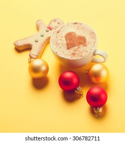 Cup of coffee and gingerbread with christmas bubbles on yellow background.