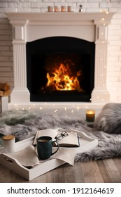 Cup of coffee, glasses and book on tray near fireplace indoors. Cozy atmosphere - Shutterstock ID 1912164619