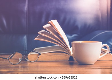 Cup of coffee with glasses and book on table in afternoon time