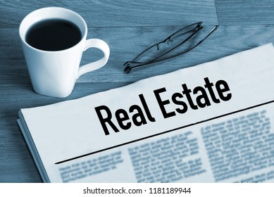 Cup of coffee, glasses and newspaper Real Estate