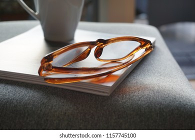 Cup of coffee and glasses on a magazine. Reading concept.