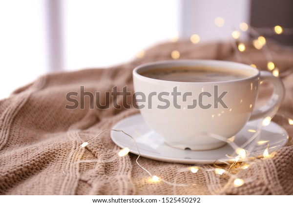 Cup of coffee with glowing garland on plaid