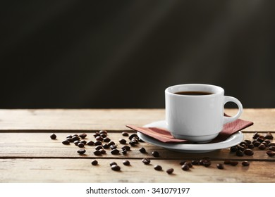 Cup of coffee and coffee grains on wooden table, on gray background