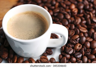 Cup of coffee and coffee grains on wooden table background