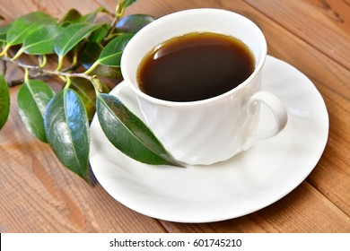 A cup of coffee with green leaves on wooden background.
