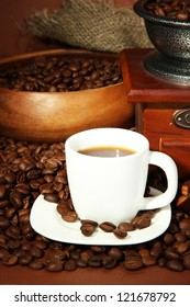 cup of coffee, grinder and coffee beans on brown background