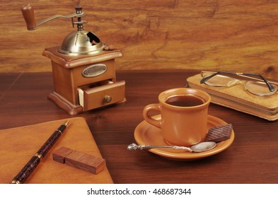 Cup of coffee, grinder, notebook and pen