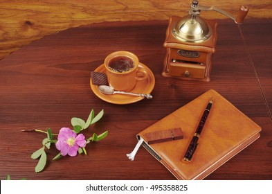 Cup of coffee, grinder, notebook, pen and flower on the table